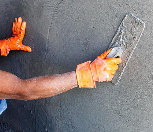 bloc-bras-ouvrier-posant-ciment-taloche
